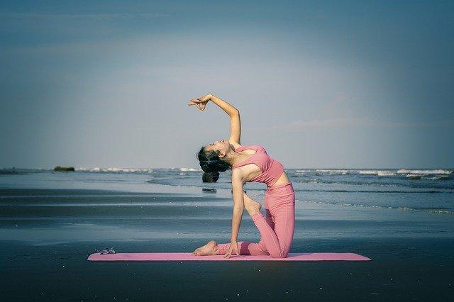 dívka cvičící jógu na pláži