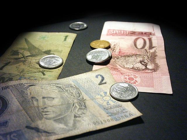 pár mincí a několik bankovek na černém podkladu